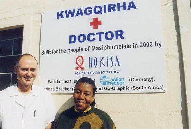 """Dr. Peter Jacka and his assistant  Babalwa in front of the new """"Doctor's House"""" at HOKISA."""