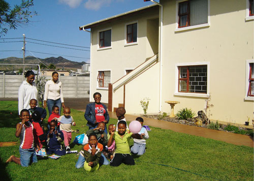 Children and residents in the garden of the HOKISA Peace House