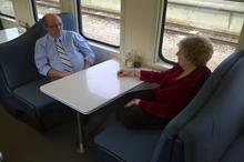 Lynette sits with Colin 'Grumpy' Boucher, Catering Manager on the train and her dear friend.