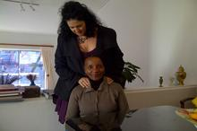 Lisa gives Sindiwe the traditional shoulder massage before the cameras roll